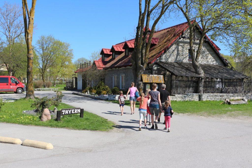"""Auf dem Bild sieht man zwei Familien, die gerade die Einfahrt zur Taverne """"Peetri Toll"""" betreten. Das Restauran ist ein älteres, aus Naturstein gebautes Gebäude mit rotem Ziegeldach."""