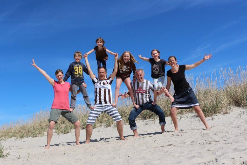 Auf dem Foto sieht man die Familien Heermann und Hilgers am Strand von Kloogaranna. Die acht Personen haben sich zu einer kleinen, menschlichen Pyramide aufgestellt: vier Erwachsene stehen nebeneinander, drei Kinder stehen jeweils dazwischen auf den Oberschenkeln der Erwachsenen, das vierte Kind steht auf den Schultern des Mannes (zweite Person von links).